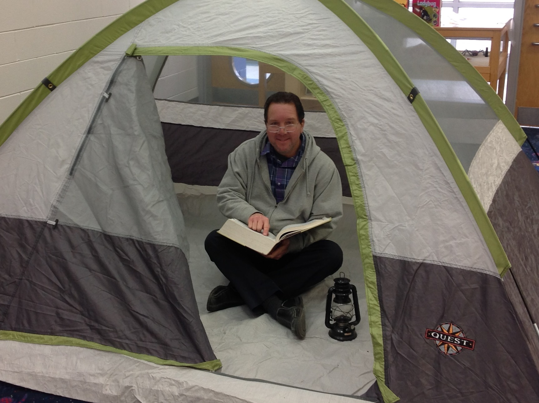Mr. Lawson reads in a tent